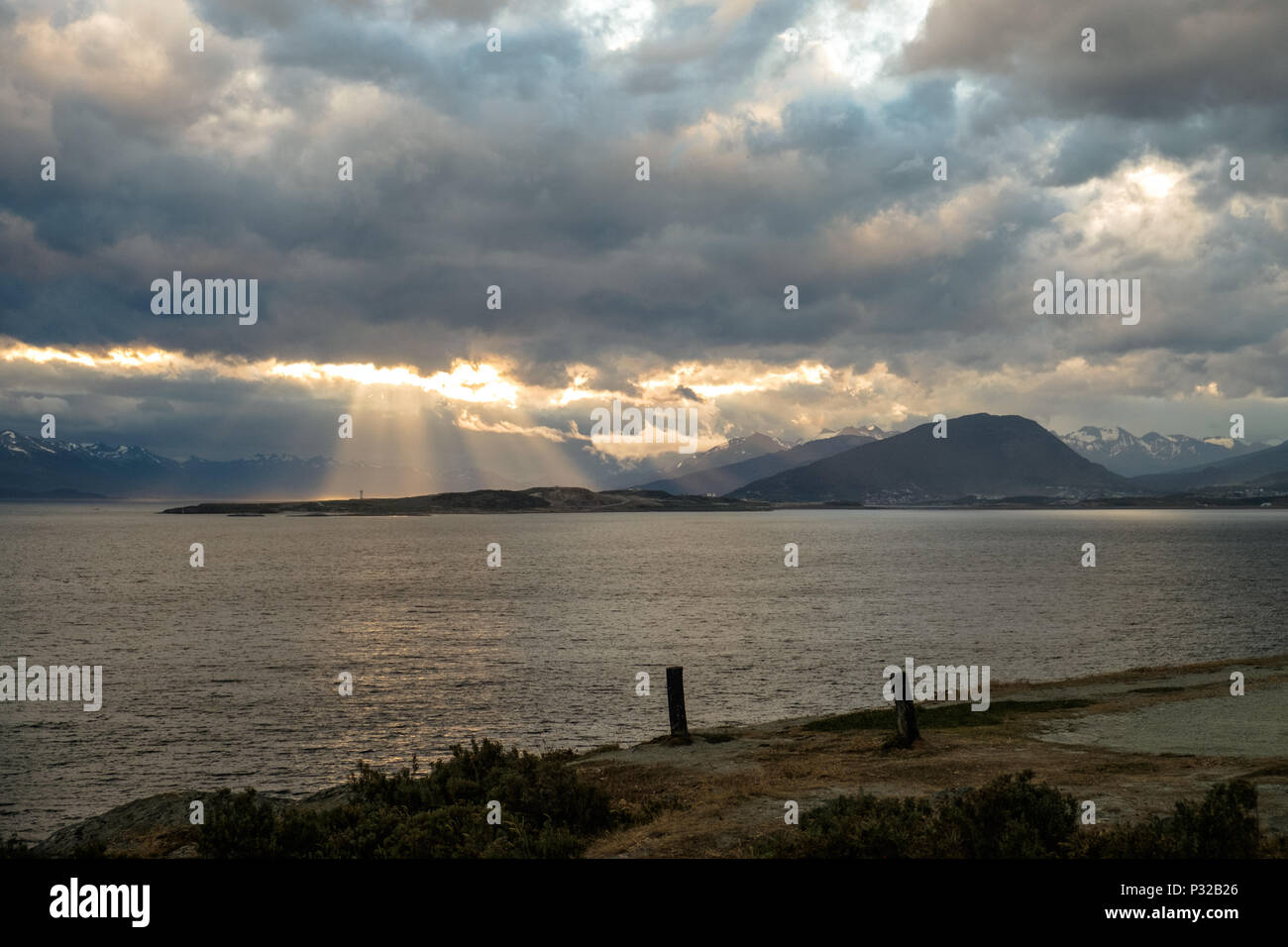 The sun finds an opening in the clouds and enlightens parts of Ushuaia. This photo is taken in Playa Larga, a popular day trip at the Beagle Channel. Stock Photo