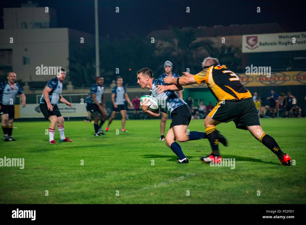 160814-N-QI061-279  MANAMA, Bahrain (Aug. 14, 2016) Lt. Cmdr. Bradley Hunsaker, assigned to the Zappers of Electronic Attack Squadron (VAQ) 130, breaks through a tackle in a rugby game between the Ike Maulers and a local rugby team, the Golden Eagles, during a port visit to the Kingdom of Bahrain. USS Dwight D. Eisenhower and its Carrier Strike Group are deployed in support of Operation Inherent Resolve, maritime security operations and theater security cooperation efforts in the U.S. 5th Fleet area of operations. (U.S. Navy photo by Mass Communication Specialist 3rd Class Nathan T. Beard) Stock Photo