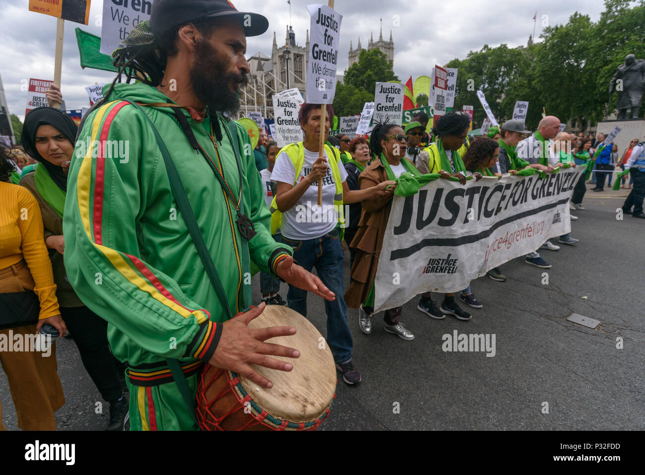 London, UK. 16th June 2018. Notting Hill community organiser Niles Hailstones drums in front of the march back from the Home Office to Downing St in solidarity with the 72 killed and the survivors of the Grenfell fire a year ago at a protest organised by Justice4Grenfell and the FBU (Fire Brigades Union.) After some speeches they marched to the Home Office for a brief protest before returning to Downing St for more speeches. Speakers complained of the many promises made by Theresa May which have been broken, despite her promise all survivors would be rehoused in 3 weeks, a year later 50% of su - Stock Image