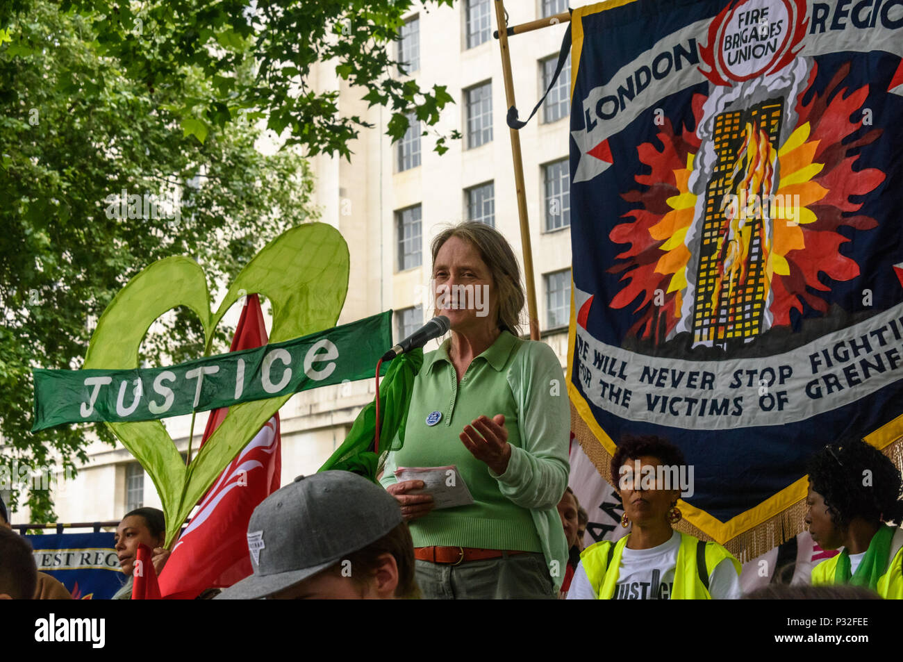 London, UK. 16th June 2018. Eileen Short of Defend Council Housing speaks at the protest at Downing St in solidarity with the 72 killed and the survivors of the Grenfell fire a year ago organised by Justice4Grenfell and the FBU (Fire Brigades Union.) After some speeches they marched to the Home Office for a brief protest before returning to Downing St for more speeches. Speakers complained of the many promises made by Theresa May which have been broken, despite her promise all survivors would be rehoused in 3 weeks, a year later 50% of survivors and displaced families are still in emergency ac - Stock Image