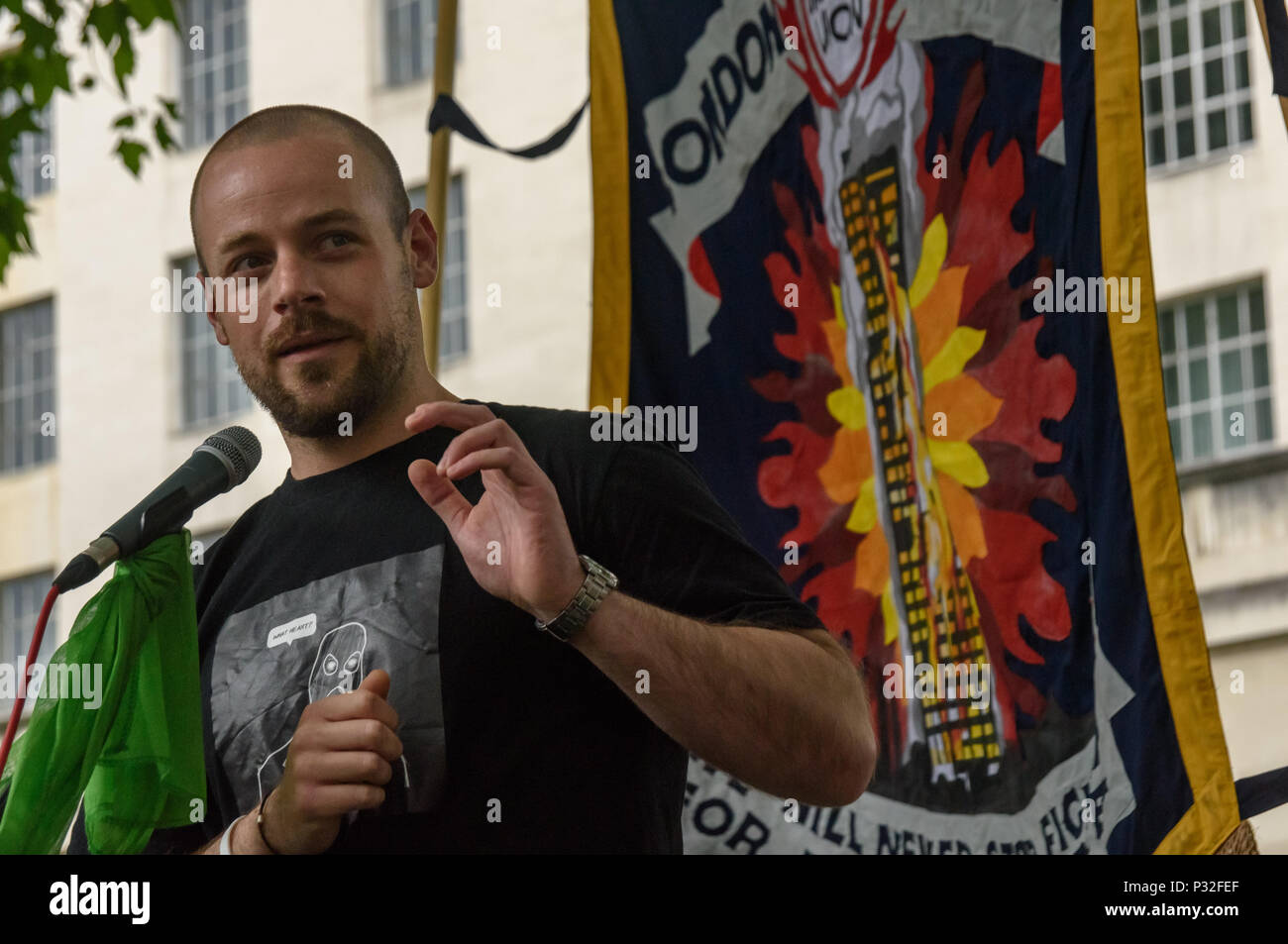 London, UK. 16th June 2018. Daniel Renwick co-director of the film about Grenfell, 'Failed by the state',  speaks at the protest at Downing St in solidarity with the 72 killed and the survivors of the Grenfell fire a year ago organised by Justice4Grenfell and the FBU (Fire Brigades Union.) After some speeches they marched to the Home Office for a brief protest before returning to Downing St for more speeches. Speakers complained of the many promises made by Theresa May which have been broken, despite her promise all survivors would be rehoused in 3 weeks, a year later 50% of survivors and disp - Stock Image