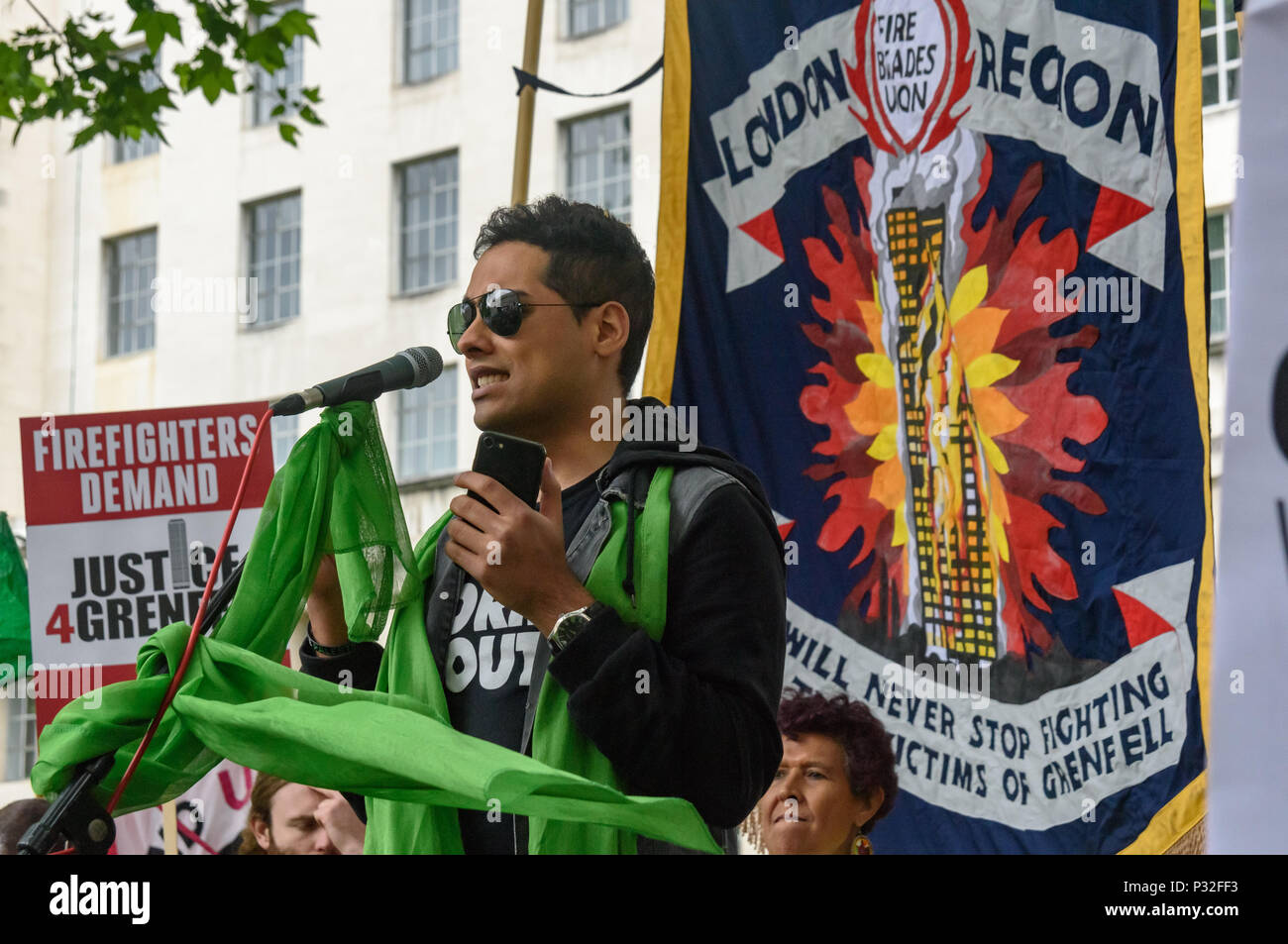 London, UK. 16th June 2018. Shabbir Lakha of People's Assembly speaks at the protest at Downing St in solidarity with the 72 killed and the survivors of the Grenfell fire a year ago organised by Justice4Grenfell and the FBU (Fire Brigades Union.) After some speeches they marched to the Home Office for a brief protest before returning to Downing St for more speeches. mm Credit: Peter Marshall/Alamy Live News - Stock Image