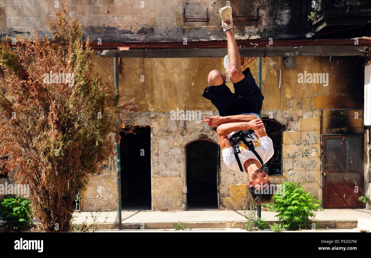 Aleppo, Syria. 8th June, 2018. A young Syrian parkour player performs a backflip in the largely-damaged part of Aleppo city, northern Syria, on June 8, 2018. With their breathtaking flips and jumping stunts, a group of young Syrians are bringing life back to the destroyed parts of Aleppo city with their electrifying Parkour performance. TO GO WITH Feature: Young Syrians revive life in old Aleppo's ruins with electrifying Parkour performance. Credit: Ammar Safarjalani/Xinhua/Alamy Live News - Stock Image