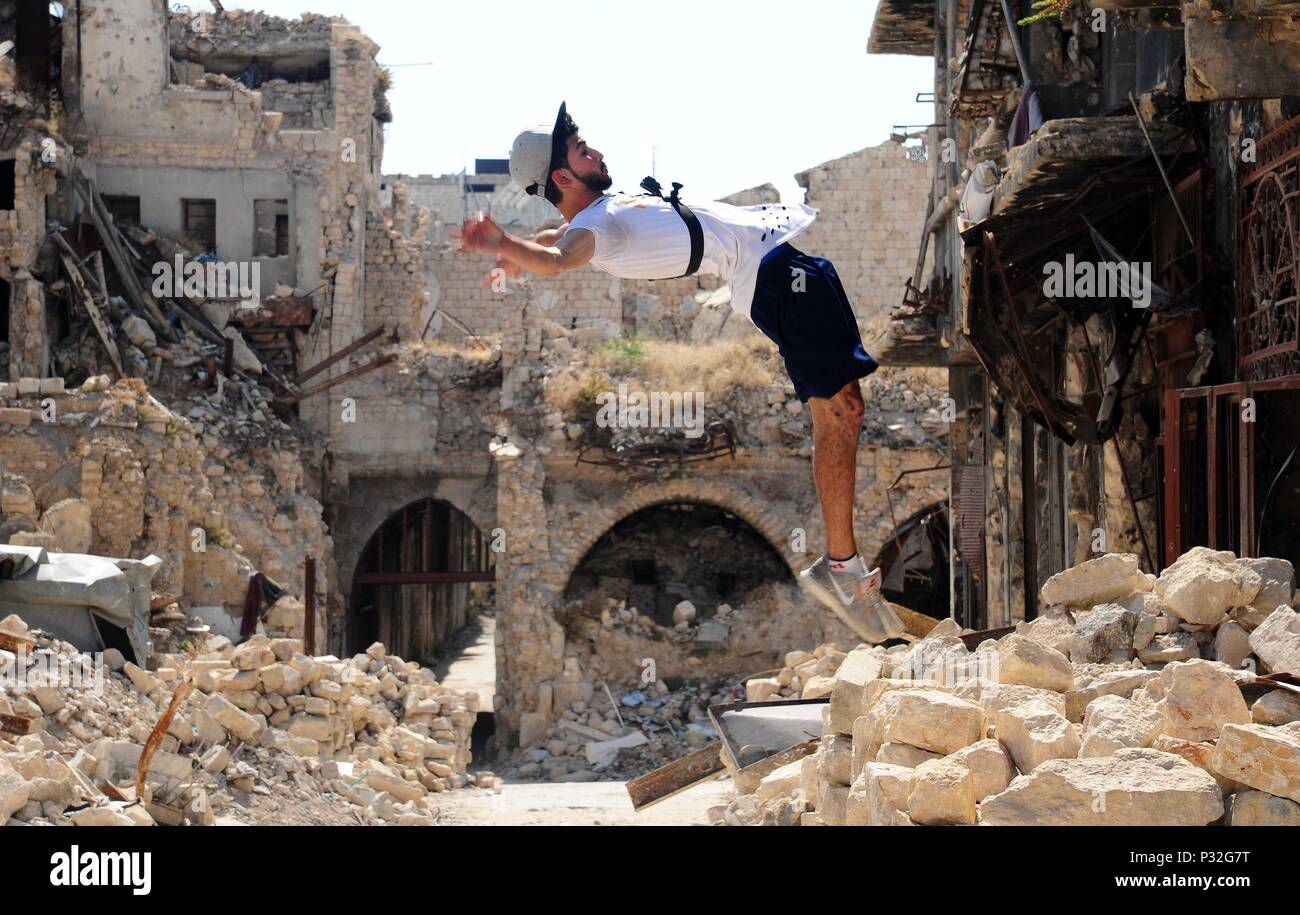 Aleppo, Syria. 8th June, 2018. A young Syrian parkour player performs a high backflip in the largely-damaged part of Aleppo city, northern Syria, on June 8, 2018. With their breathtaking flips and jumping stunts, a group of young Syrians are bringing life back to the destroyed parts of Aleppo city with their electrifying Parkour performance. TO GO WITH Feature: Young Syrians revive life in old Aleppo's ruins with electrifying Parkour performance. Credit: Ammar Safarjalani/Xinhua/Alamy Live News - Stock Image