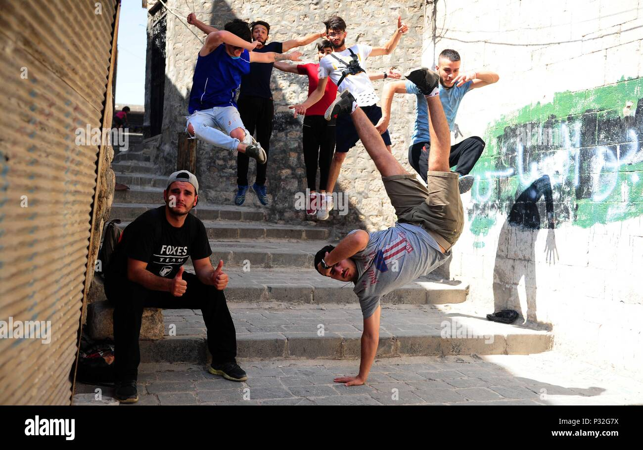 Aleppo, Syria. 8th June, 2018. Young Syrian parkour players perform a coordinated jump in the largely-damaged part of Aleppo city, northern Syria, on June 8, 2018. With their breathtaking flips and jumping stunts, a group of young Syrians are bringing life back to the destroyed parts of Aleppo city with their electrifying Parkour performance. TO GO WITH Feature: Young Syrians revive life in old Aleppo's ruins with electrifying Parkour performance. Credit: Ammar Safarjalani/Xinhua/Alamy Live News - Stock Image