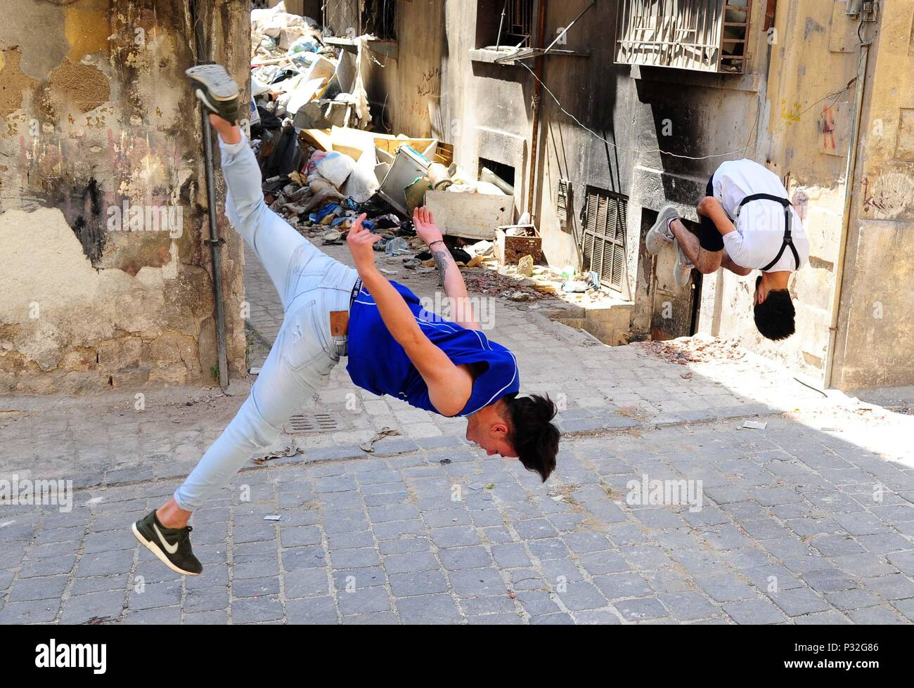 Aleppo, Syria. 8th June, 2018. Young Syrian parkour players perform front and backflips in the largely-damaged part of Aleppo city, northern Syria, on June 8, 2018. With their breathtaking flips and jumping stunts, a group of young Syrians are bringing life back to the destroyed parts of Aleppo city with their electrifying Parkour performance. TO GO WITH Feature: Young Syrians revive life in old Aleppo's ruins with electrifying Parkour performance. Credit: Ammar Safarjalani/Xinhua/Alamy Live News - Stock Image