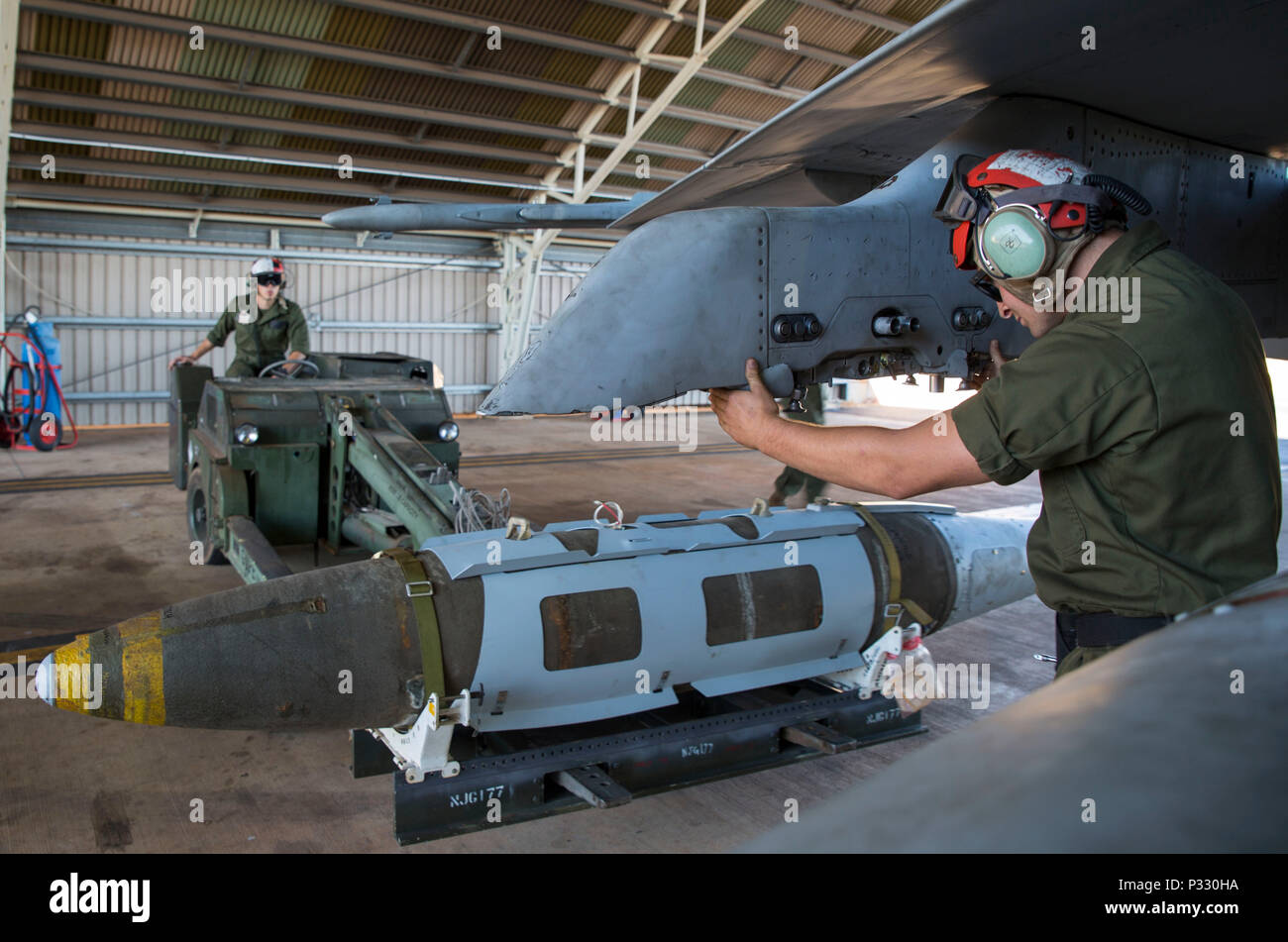 U.S. Marine Corps Lance Cpl. Trevor Serenelli, ordnance Marine assigned to Marine Fighter Attack Squadron (VMFA) 122, helps U.S. Marine Corps Cpl. Blake Uhden, ordnance Marine assigned to VMFA-122, guide a bomb onto an aircraft during Southern Frontier at Royal Australian Air Force Base Tindal, Australia, Aug. 26, 2016. VMFA-122 dropped hundreds of thousands of pounds of ordnance while conducting close air support missions for ground combat units at the Bradshaw Range Complex. Southern Frontier is a three week unit level training evolution helping the flying squadron gain qualifications and ex - Stock Image
