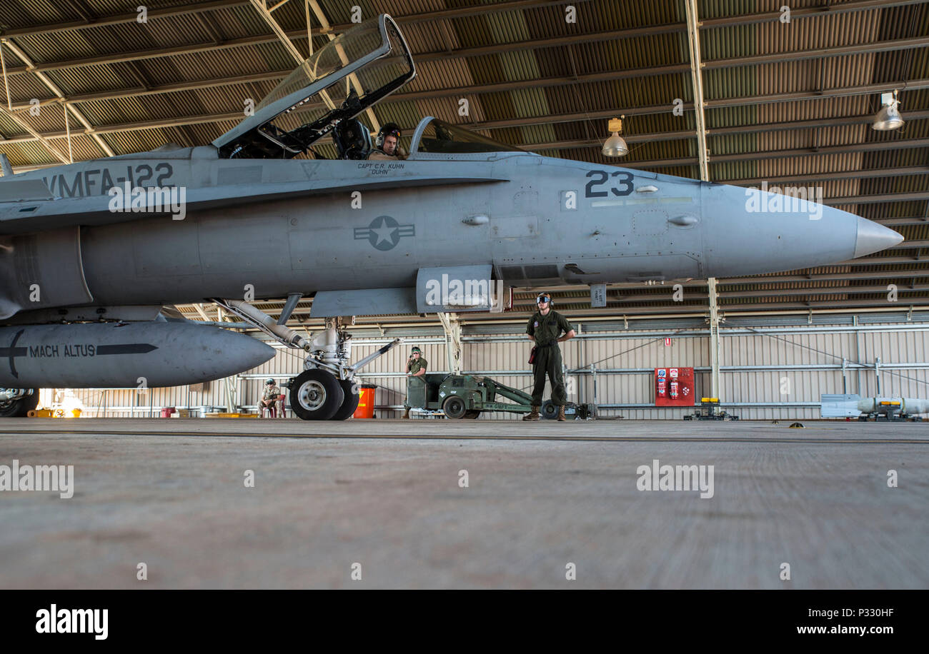 U.S. Marine Corps Maj. David Dunsworth, an F/A-18C Hornet pilot with Marine Fighter Attack Squadron (VMFA) 122, completes a preflight check as Lance Cpl. Luke Zeisloft, a powerline Marine assigned to VMFA-122, stands by during Southern Frontier at Royal Australian Air Force Base Tindal, Australia, Aug. 24, 2016. VMFA-122 provided close air support to ground units at Bradshaw Range Complex during the training. Southern Frontier is a three week unit level training evolution helping the flying squadron gain qualifications and experience in low altitude, air ground, high explosive ordnance deliver - Stock Image