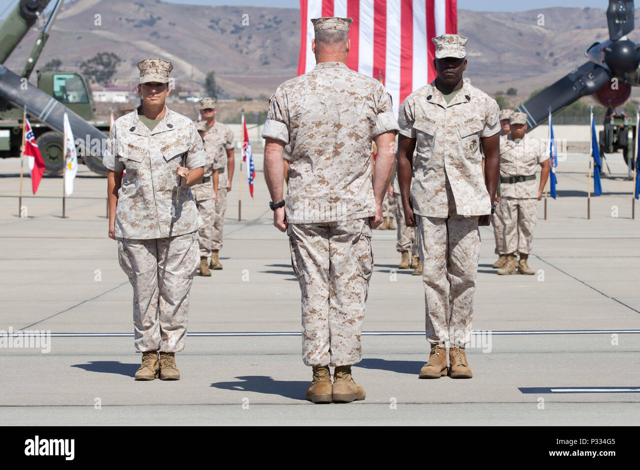 U.S. Marine Corps Sgt. Maj. Karyl J. Sisneros (left), Col. Ian R. Clark (center), and Sgt. Maj. Reginald Robinson stand at attention during the MCAS Camp Pendleton post and relief ceremony on Camp Pendleton, Calif., Aug. 31, 2016. (U.S. Marine Corps photo by Cpl. Tyler Dietrich) - Stock Image