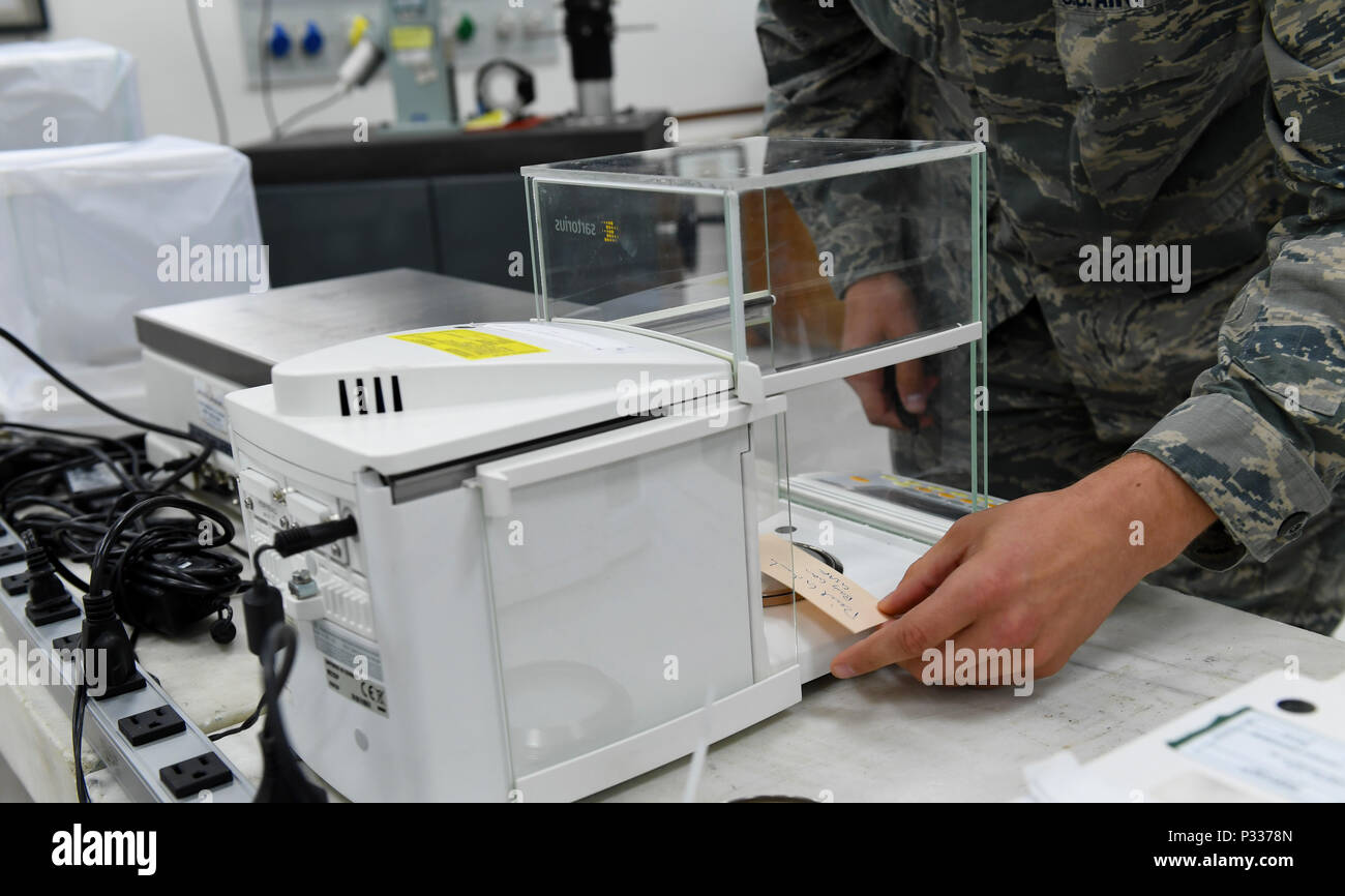 Senior Airman Giuseppe Ray, 86th Maintenance Squadron precision measurement equipment laboratory calibration equipment technician, weighs ink from a hand-written note during an 86th Maintenance Group demonstration Aug. 31, 2016 at Ramstein Air Base, Germany. The 86th MXG operates the largest precision measurement equipment laboratory in the Air Force. Ray determined that the ink weighed 2,470 micrograms. (U.S. Air Force photo/Senior Airman Tryphena Mayhugh) - Stock Image