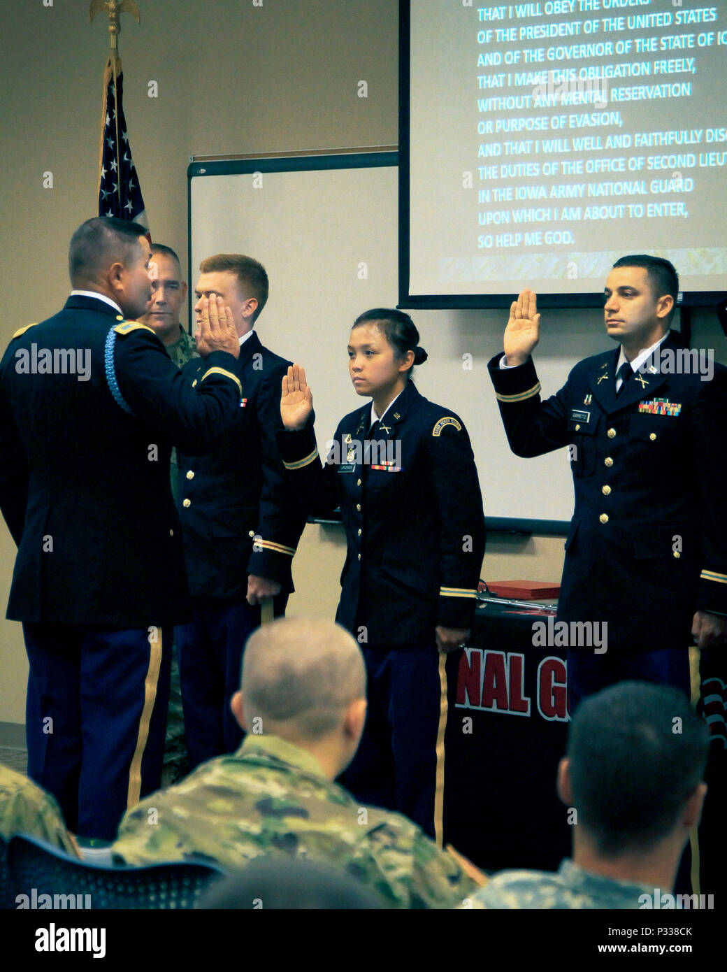 Iowa Army National Guard 2nd Lt. Trang Jorgensen (center), Headquarters and Headquarters Company, 1st Battalion, 168th Infantry, is administered the Oath of Office by Col. Steve Kremer, 185th Regional Training Institute commandant, alongside her peers at their commissioning  ceremony on Camp Dodge Joint Maneuver Training Center in Johnston, Iowa, on Aug. 20. Jorgensen is the first female officer in the Iowa National Guard to select infantry as her branch. (U.S. Army National Guard photo by Sgt. Christie Smith) - Stock Image