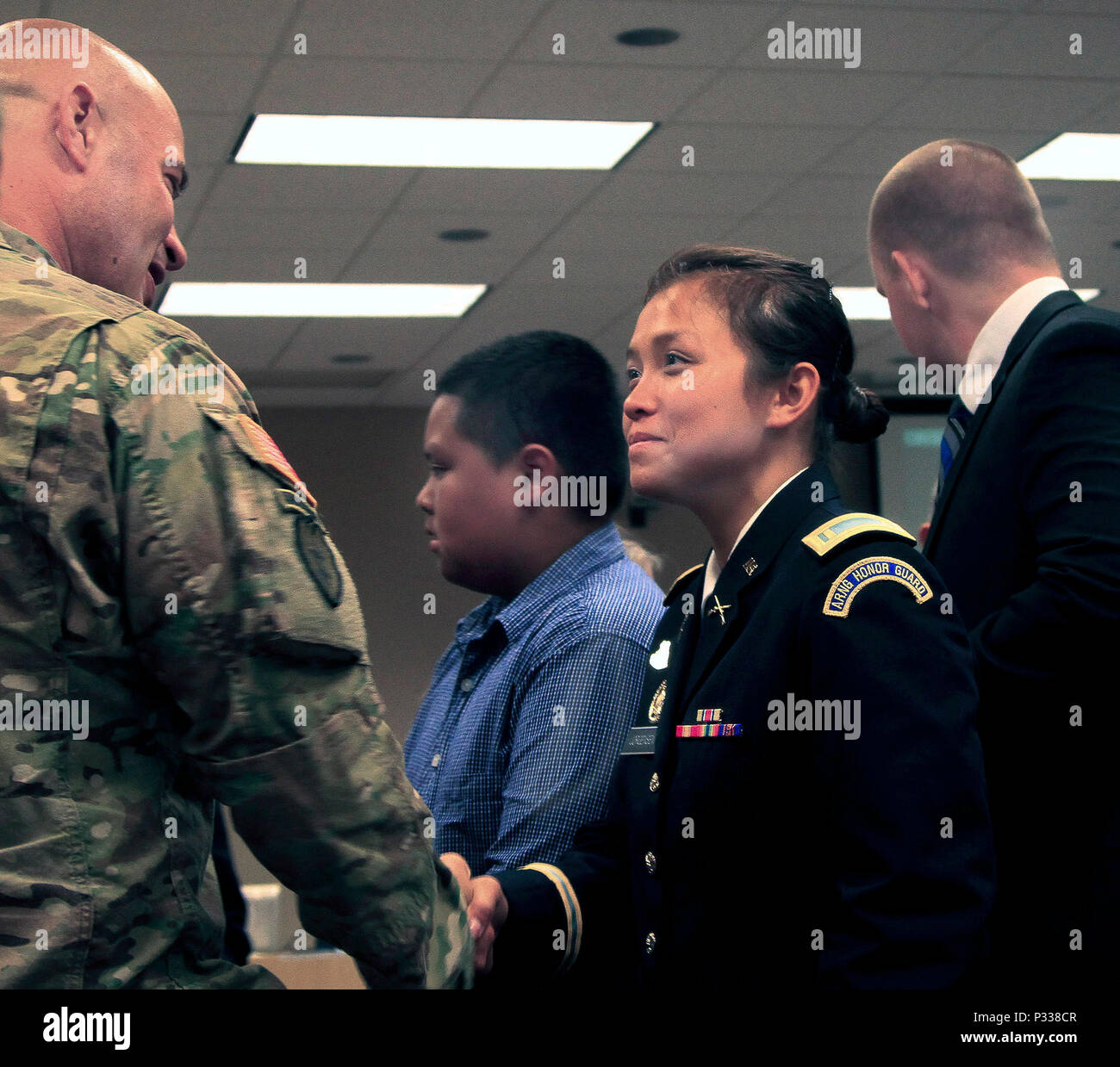 Iowa Army National Guard 2nd Lt. Trang Jorgensen, Headquarters and Headquarters Company, 1st Battalion, 168th Infantry, shakes hands with Lt. Col. Aaron Baugher, 1st Battalion, 168th Infantry Battalion commander, after receiving her commission during a ceremony on Camp Dodge Joint Maneuver Training Center in Johnston, Iowa, on Aug. 20. Jorgensen is the first female officer in the Iowa Army National Guard to select a combat arms branch. (U.S. Army National Guard photo by Sgt. Christie Smith) - Stock Image
