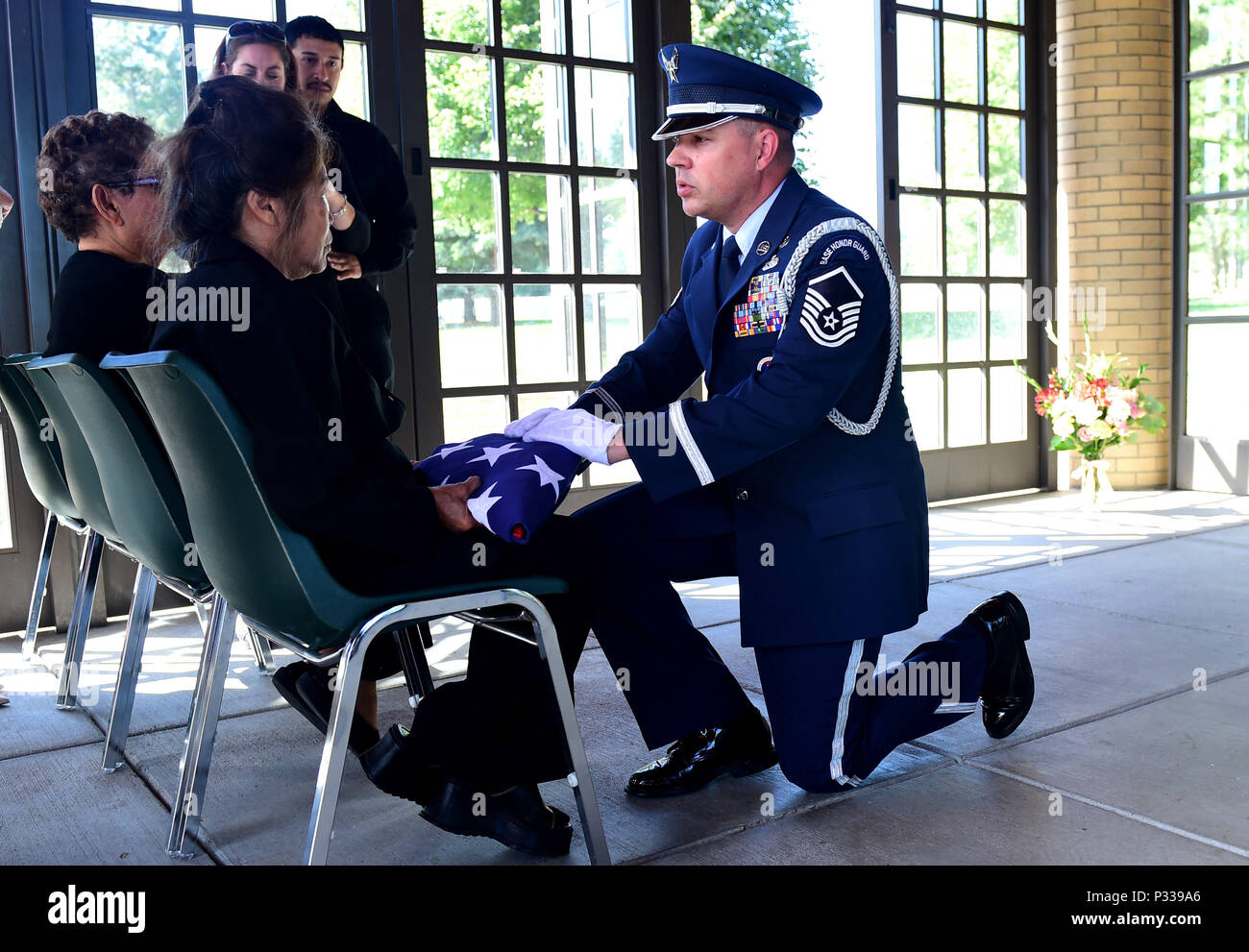 Master Sgt. Wolfram Stumpf, U.S. Air Force Mile High Honor Guard member, presents a widow an American flag during the funeral for her husband August 30, 2016, at Fort Logan National Cemetery, Colo. The American flag is presented during a military honors funeral as a lasting tribute to the veteran's family. (U.S. Air Force photo by Airman 1st Class Gabrielle Spradling/Released) Stock Photo