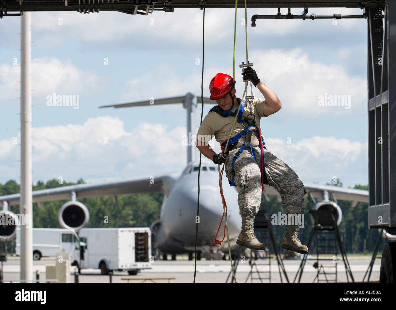 Senior Airman Dallas Gullion, 436th Civil Engineer Squadron firefighter, repels off of a mobile T-tail maintenance stand Aug. 17, 2016, at Dover Air Force Base, Del. Gullion learned rope rescue techniques during a Rescue Technician Course. (U.S. Air Force photo by Senior Airman Zachary Cacicia) - Stock Image