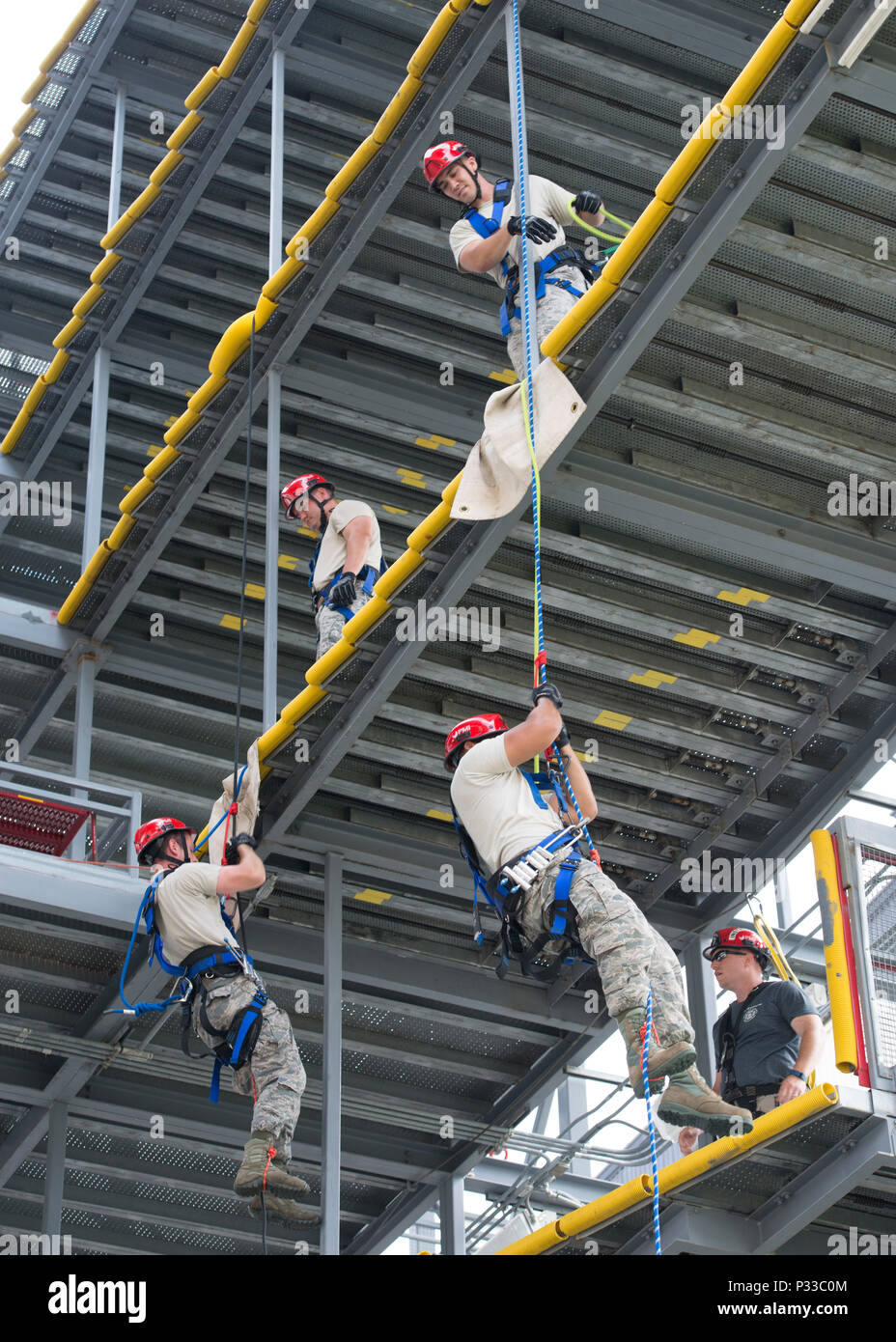 Four firefighters assigned to the 436th Civil Engineer Squadron Fire Department practice climbing and repelling during a Rescue Technician Course Aug. 18, 2016, from a mobile T-tail maintenance stand on Dover Air Force Base, Del. The T-tail stand allowed for a multitude of anchor points and levels to conduct training. (U.S. Air Force photo by Senior Airman Zachary Cacicia) - Stock Image