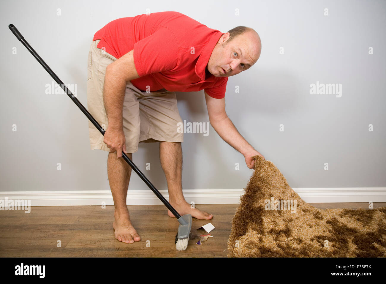 A man hiding rubbish under the carpet, sayings and concepts. - Stock Image