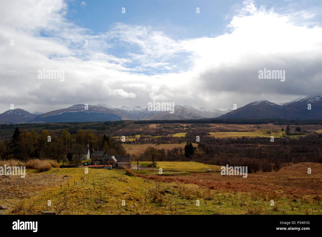 Landscape view over the Scottish Highlands out over rolling hills towards mountains with blue sky and clouds. - Stock Image