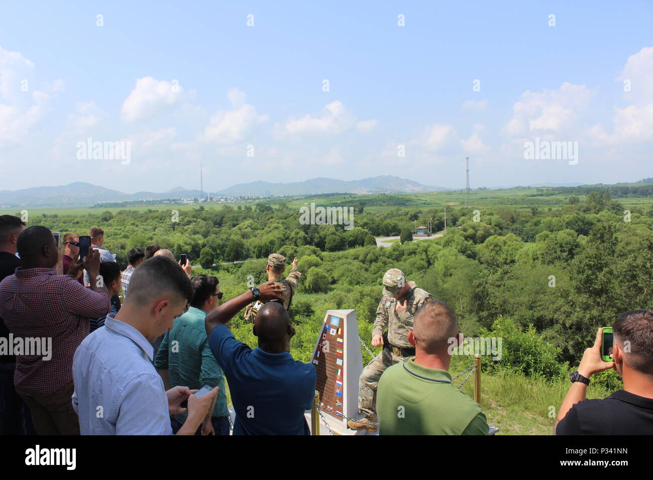 """Soldiers from 2nd Battalion, 8th Cavalry Regiment """"Stallions,"""" 1st Armored Brigade Combat Team, 1st Cavalry Division listen and take photos of the """"Bridge of No Return"""" and Kijong-dong """"peace village"""" in North Korea, while U.S. Army military police explain the significance of these sites. Soldiers visited Camp Bonifas, South Korea, as well as the Joint Security Area in the Korean Demilitarized Zone, the """"Bridge of No Return"""" and several other points of interest, during a tour Aug. 16. (U.S. Army photo by Spc. Jeremy Reuse, 2nd Battalion, 8th Cavalry Regiment, 1st Armored Brigade Combat Team, 1 Stock Photo"""