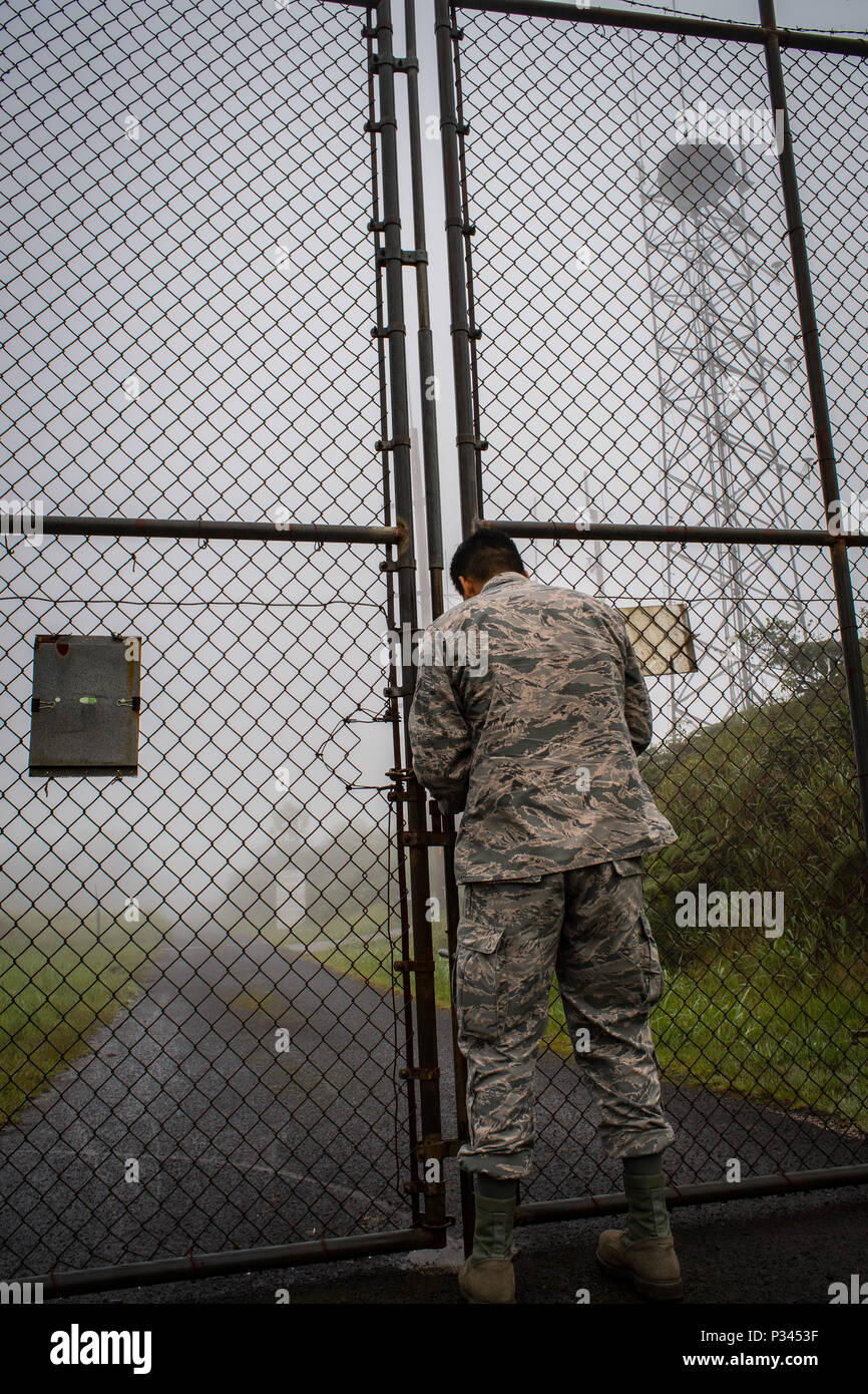 Airman 1st Class Kevin Plunkett, a radio frequency transmissions systems technician with the Hawaii Air National Guard's 169th Air Defense Squadron, unlocks the gates to Mt. Ka'ala Air Force station (AFS), Aug. 12, 2016, Oahu, Hawaii. Mt. Ka'ala AFS sits atop the highest point on the island of Oahu and houses the 169th ADS's radar equipment, which is used to monitor the airspace around the Hawaiian Islands. (U.S. Air Force photo by Tech. Sgt. Brandon Shapiro) Stock Photo