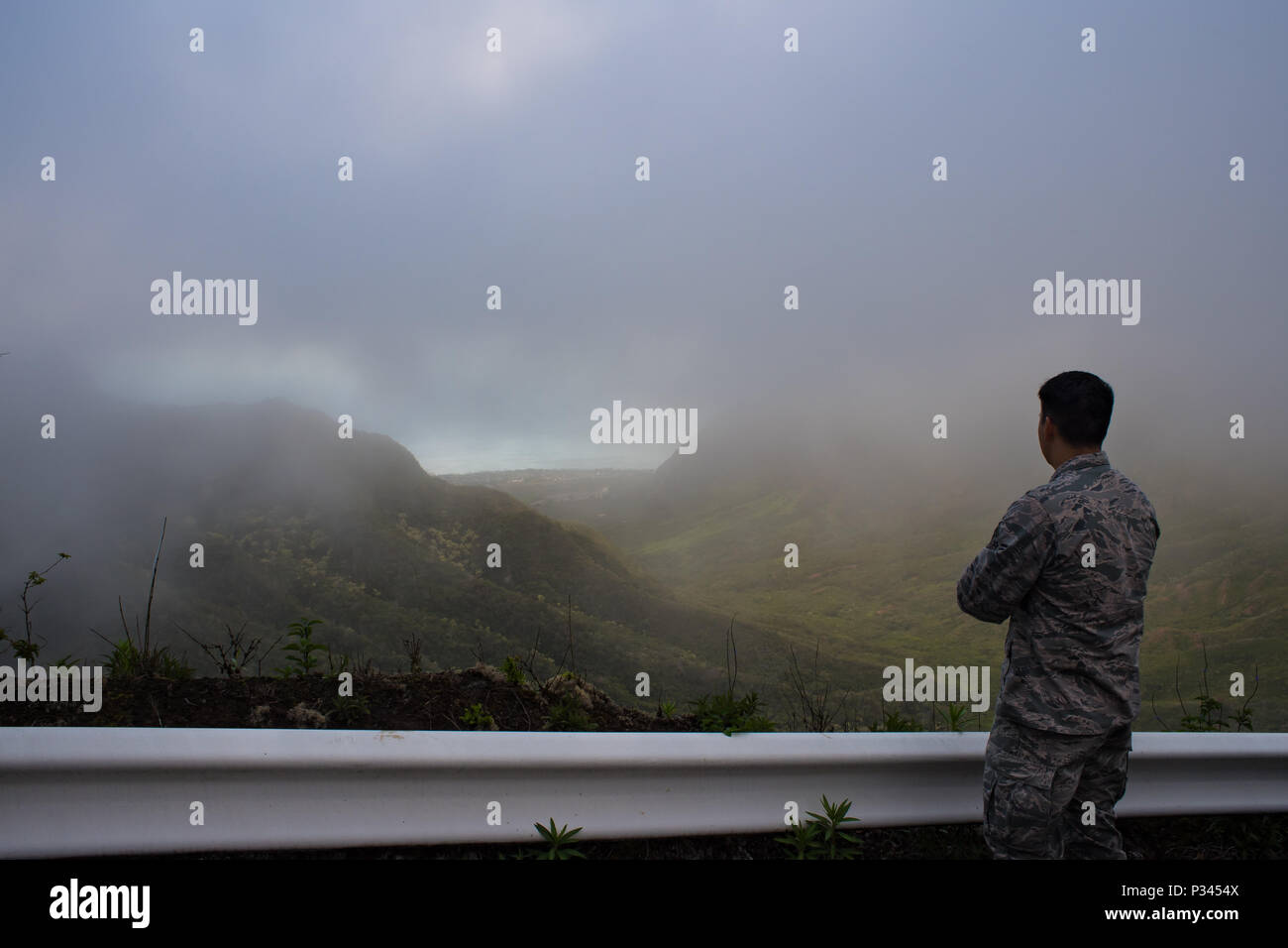 Airman 1st Class Kevin Plunkett, a radio frequency transmissions systems technician with the Hawaii Air National Guard's 169th Air Defense Squadron, looks out over the island of Oahu from the Ka'ala Air Force Station's main access road, Aug. 12, 2016, Oahu, Hawaii. The Hawaii Air National Guard oversees the monitoring of the airspace around the Hawaiian Islands at Wheeler Army Airfield, Oahu, Hawaii. (U.S. Air Force photo by Tech. Sgt. Brandon Shapiro) Stock Photo