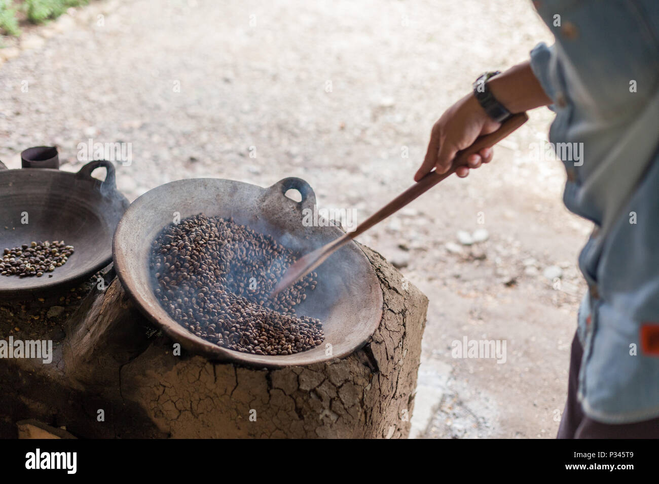 Master roasters manually roast coffee beans over a wood-fired stove near Banyuwangi, Java, Indonesia - Stock Image