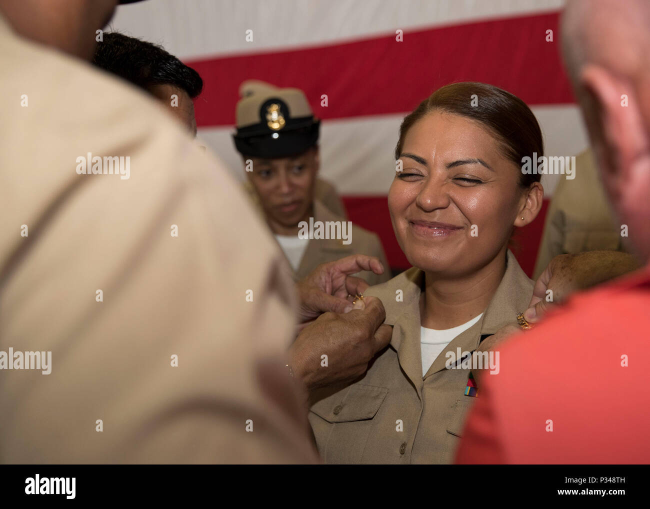 NORFOLK, Va. (June 12, 2018) -- Senior Chief Ship's Serviceman Angela Zamora, from Jersey City, New Jersey, assigned to USS Gerald R. Ford's (CVN 78) supply department, is pinned to her current rank by her family during a senior chief petty officer pinning ceremony in the ship's hangar bay. Ford had 14 chief petty officers selected to the rank of senior chief petty officer. (U.S. Navy photo by Mass Communication Specialist 3rd Class Ryan Carter) - Stock Image
