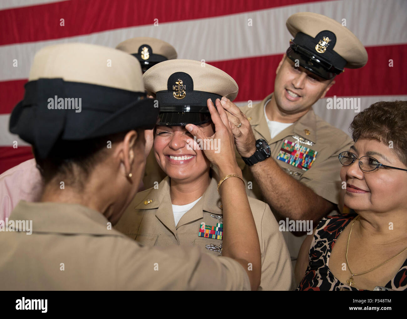NORFOLK, Va. (June 12, 2018) -- Senior Chief Ship's Serviceman Angela Zamora, from Jersey City, New Jersey, assigned to USS Gerald R. Ford's (CVN 78) supply department, is covered by Master Chief Logistics Specialist German Padilla and Master Chief Ship Serviceman Monique Chatman during a senior chief petty officer pinning ceremony in the ship's hangar bay. Ford had 14 chief petty officers selected to the rank of senior chief petty officer. (U.S. Navy photo by Mass Communication Specialist 3rd Class Ryan Carter) - Stock Image