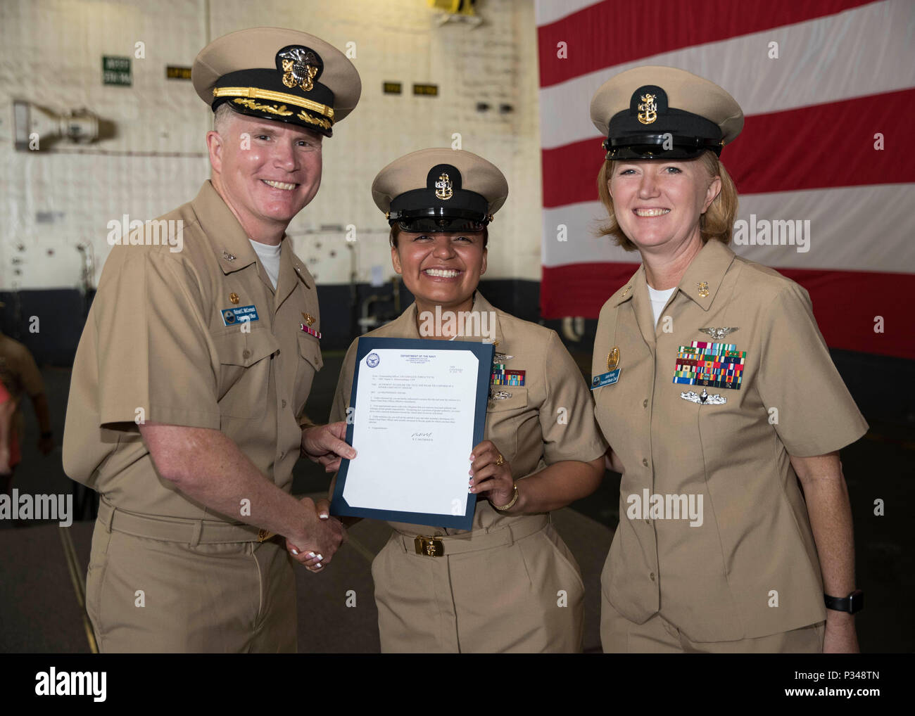 NORFOLK, Va. (June 12, 2018) -- Senior Chief Ship's Serviceman Angela Zamora, from Jersey City, New Jersey, assigned to USS Gerald R. Ford's (CVN 78) supply department, receives her frocking letter from Capt. Richard McCormack, Ford's commanding officer, and Command Master Chief Laura Nunley, Ford's command master chief, during a senior chief petty officer pinning ceremony in the ship's hangar bay. Ford had 14 chief petty officers selected to the rank of senior chief petty officer. (U.S. Navy photo by Mass Communication Specialist 3rd Class Ryan Carter) - Stock Image