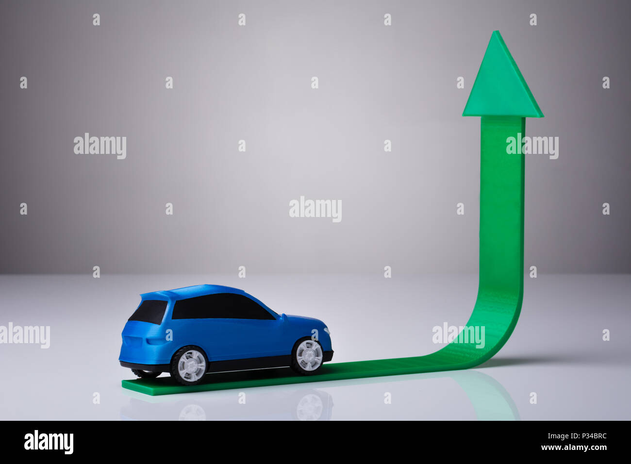 Blue Car Driving On Green Upward Arrow Against Gray Background - Stock Image