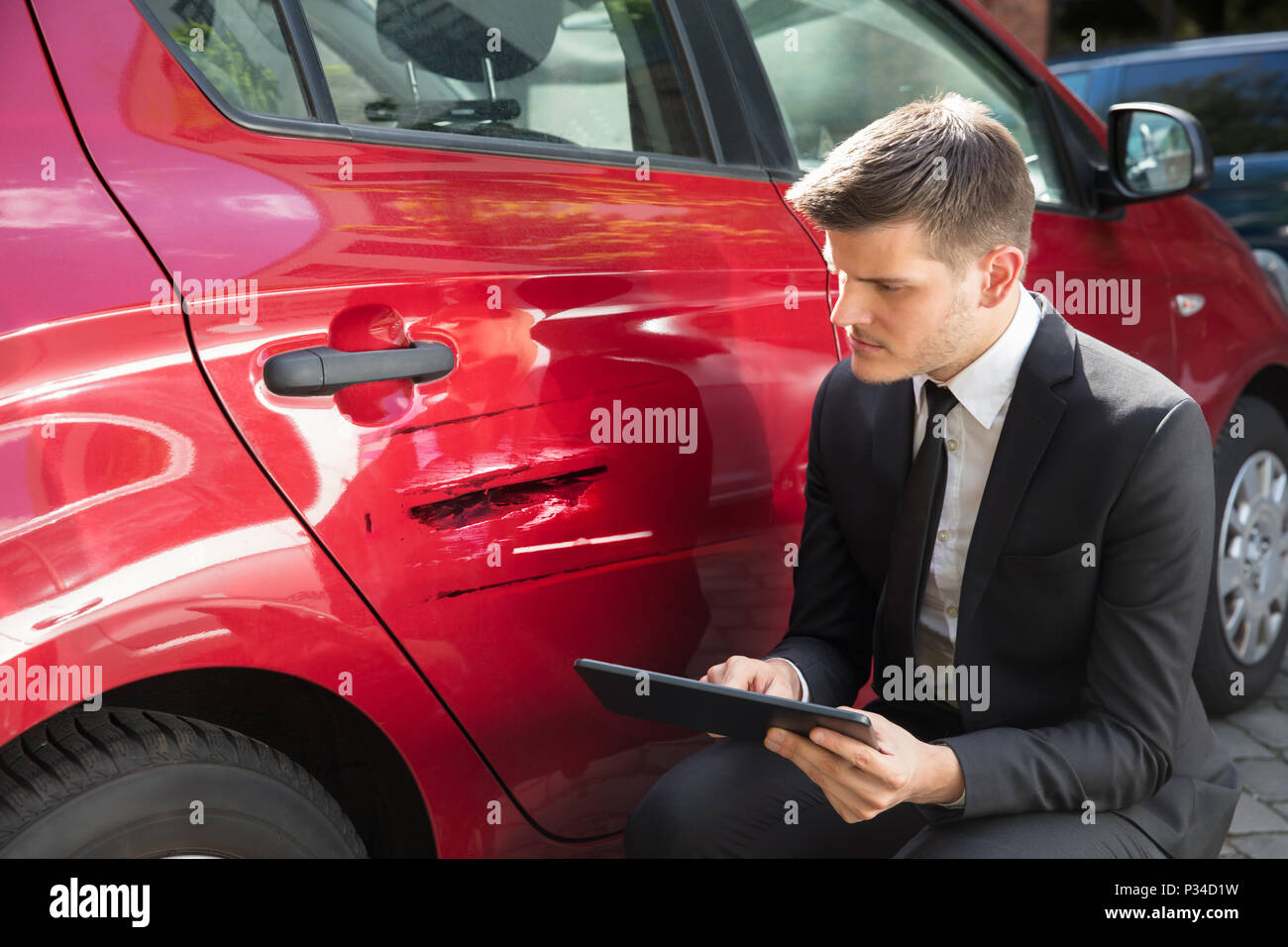 Insurance Agent Filling Insurance Form Near Damaged Red Car - Stock Image