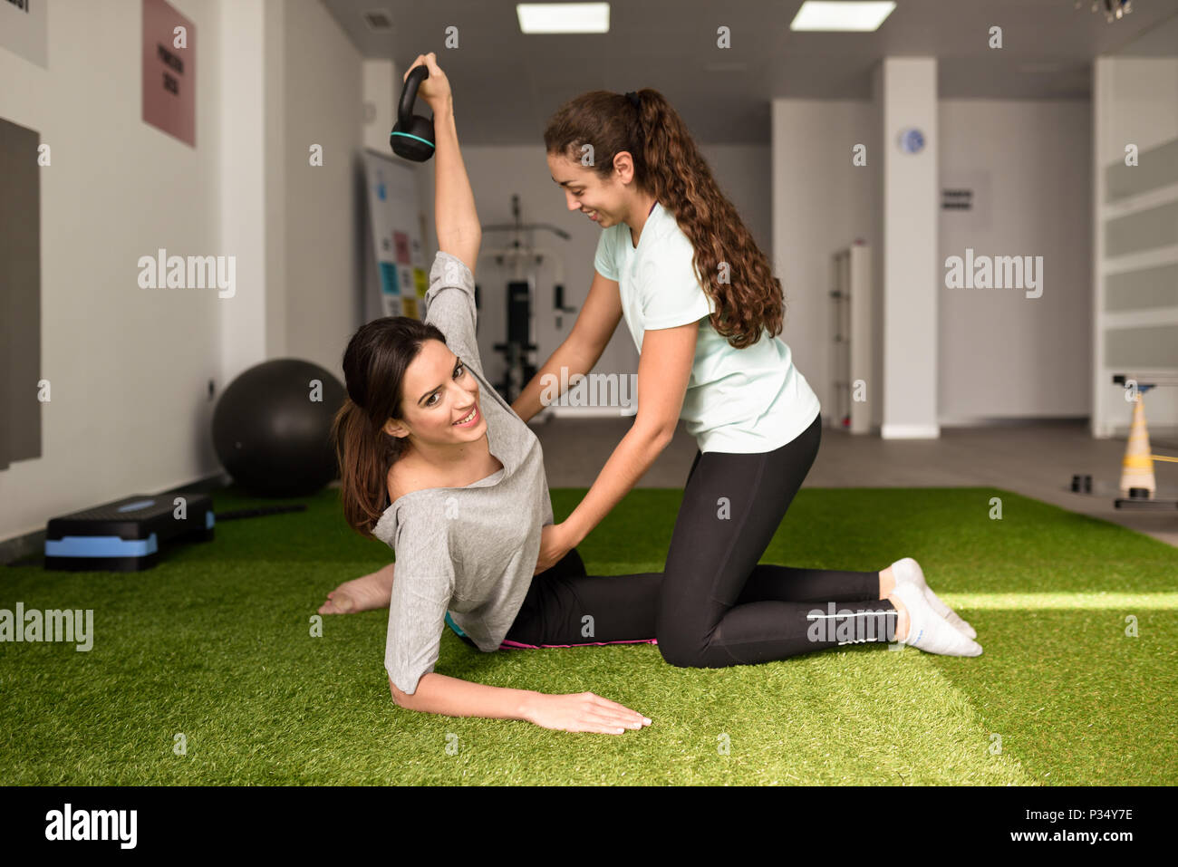 Physical therapist assisting young caucasian woman with exercise with dumbbell during rehabilitation in the gym at hospital. Female physiotherapist tr - Stock Image