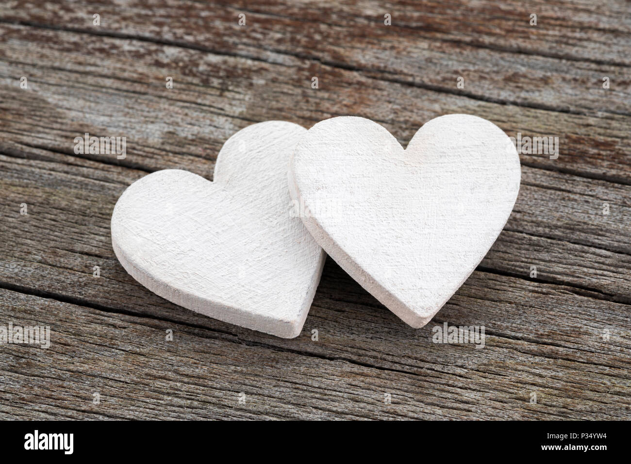 Two hearts on old wooden background - Stock Image