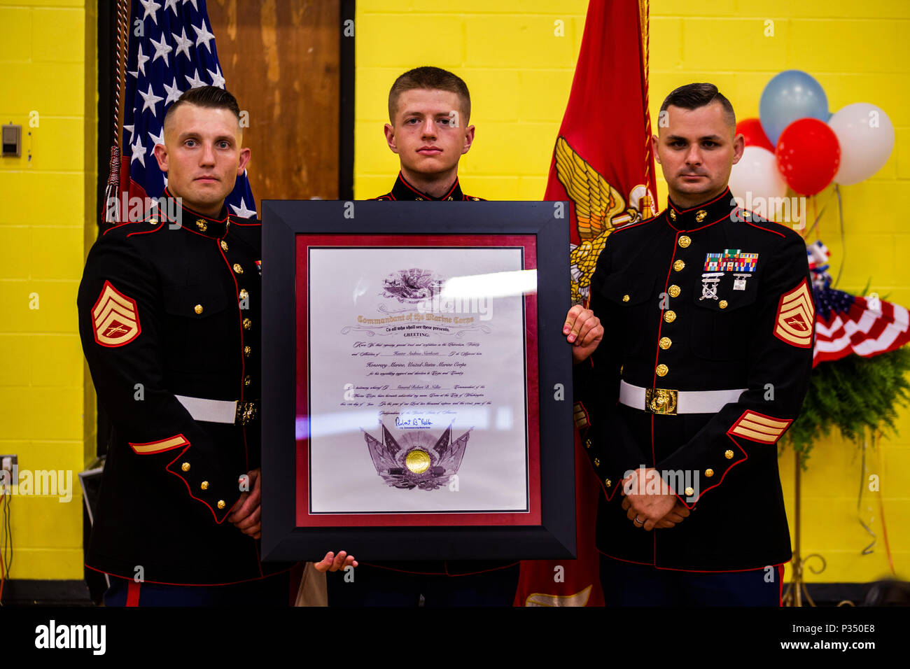 pfc gavin g northcutt holds the honorary marine award posthumously for his cousin hunter a northcutt next to staff sgt james b benham left and