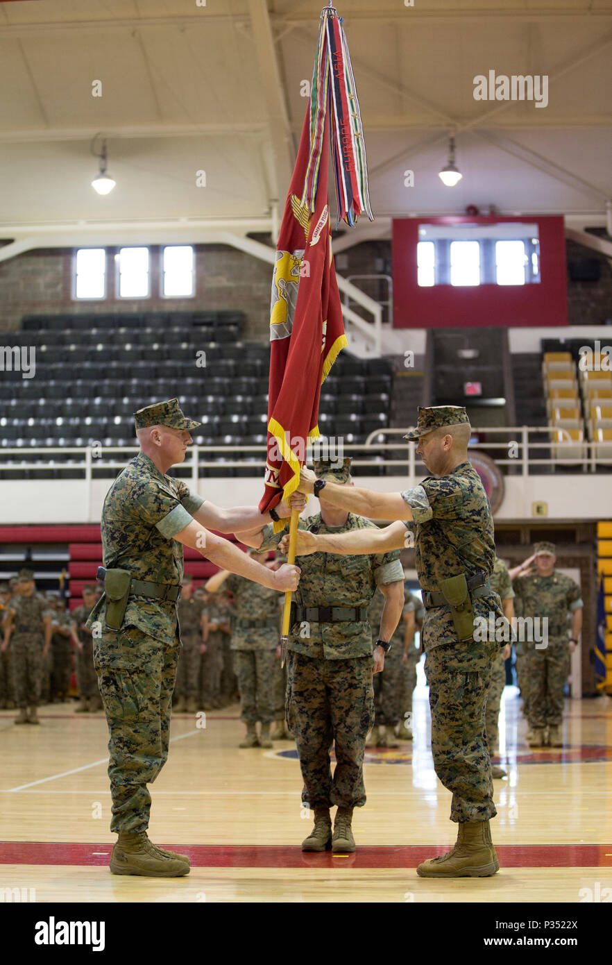 U.S. Marine Corps Lt. Col. Charles D. Nicol, left, incoming commanding officer of 2nd Tank Battalion, 2nd Marine Division, receives the unit colors from Lt. Col. Lance J. Langfeldt, right, outgoing commanding officer of 2nd Tank Battalion, during a change of command ceremony at Camp Lejeune, N.C., June 15, 2018. During the ceremony, Langfeldt relinquished command of the unit to Nicol. (U.S. Marine Corps photo by Cpl. Melanye Martinez) - Stock Image