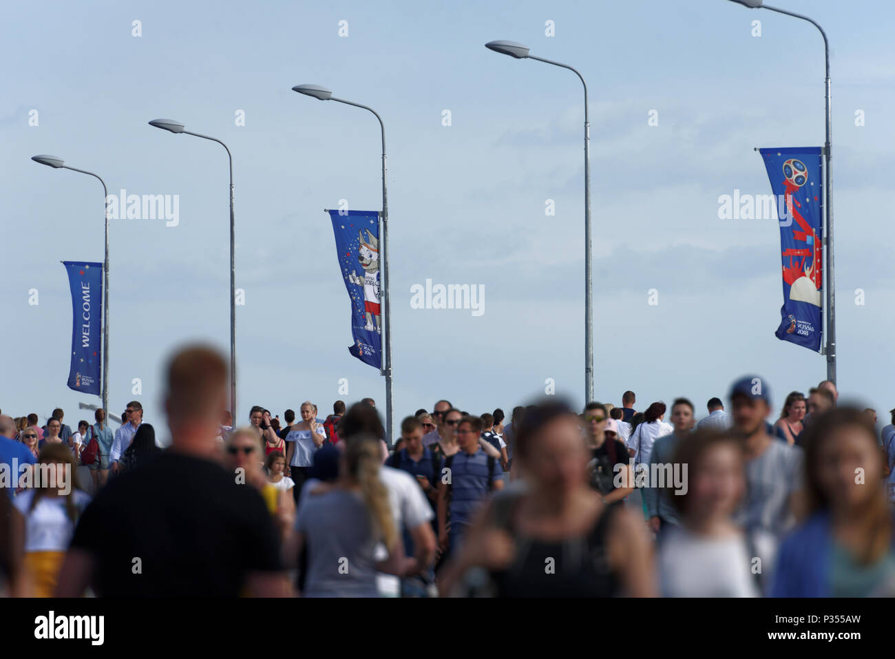 St. Petersburg, Russia - June 16, 2018: People on Yachtenny bridge under FIFA World Cup Russia 2018 banners with Zabivaka mascot. Saint Petersburg hos - Stock Image