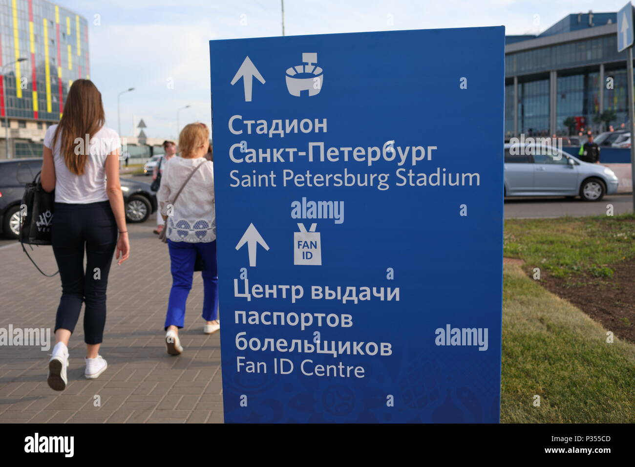 St. Petersburg, Russia - June 16, 2018: People at the sign pointing direction to Saint Petersburg Stadium and Fan ID Center during FIFA World Cup Russ - Stock Image