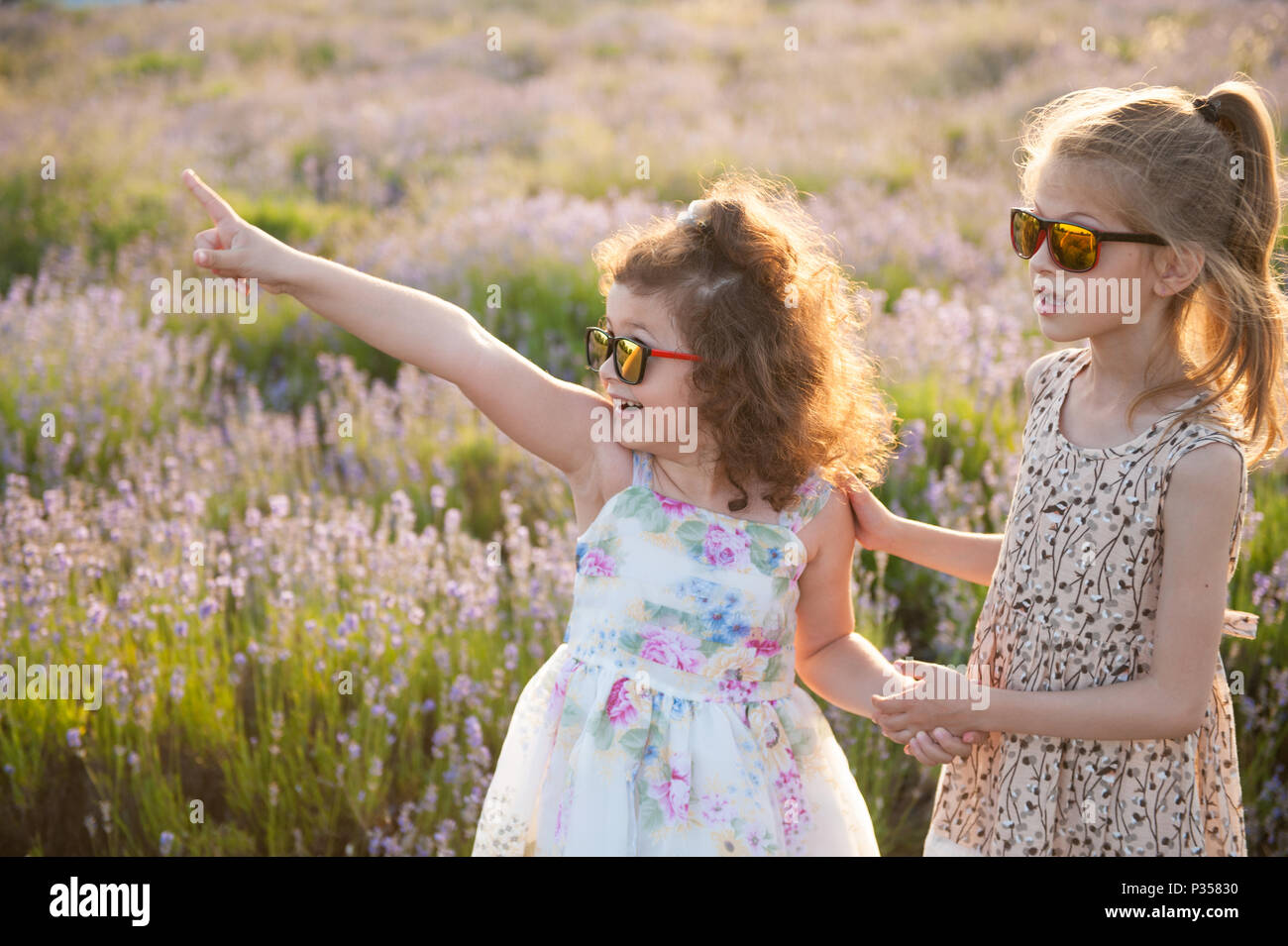 3d6ec10da646 two cute little girls in sunglasses one of them point her finger at  something