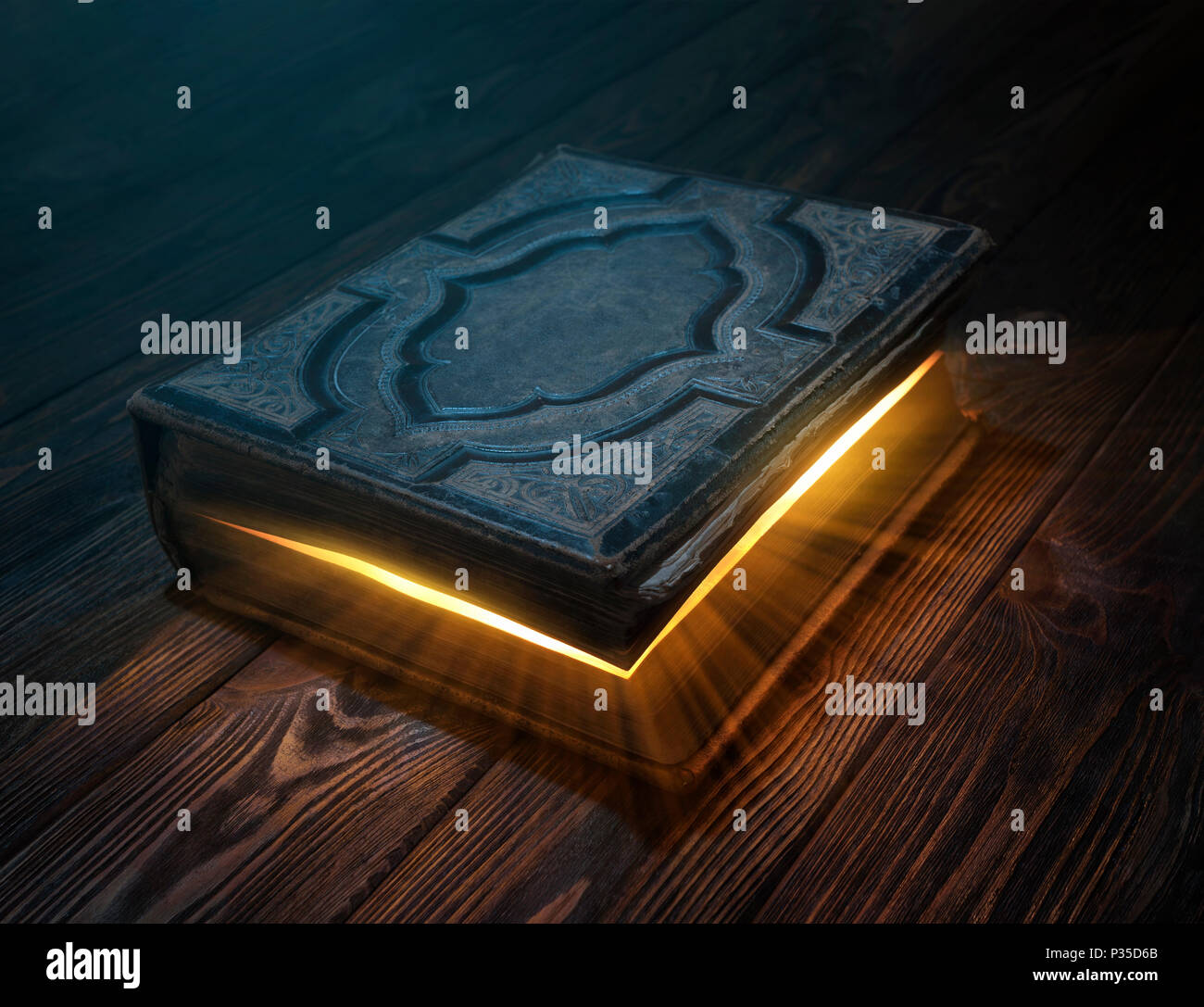 Old magic book on wooden table with light rays coming out form instide - Stock Image