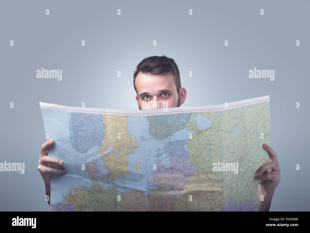 Handsome young man holding map  - Stock Image