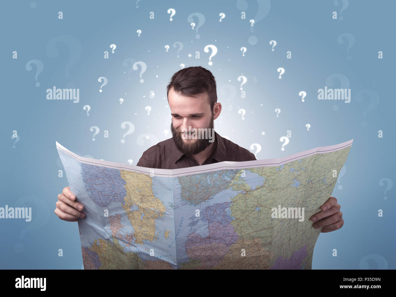 Handsome young man holding a map with white question marks above his head - Stock Image