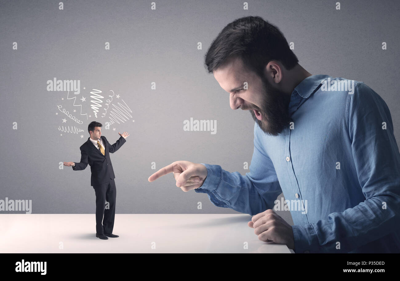 Young professional businessman being angry with an other miniature businessman who has scribbles above his head - Stock Image