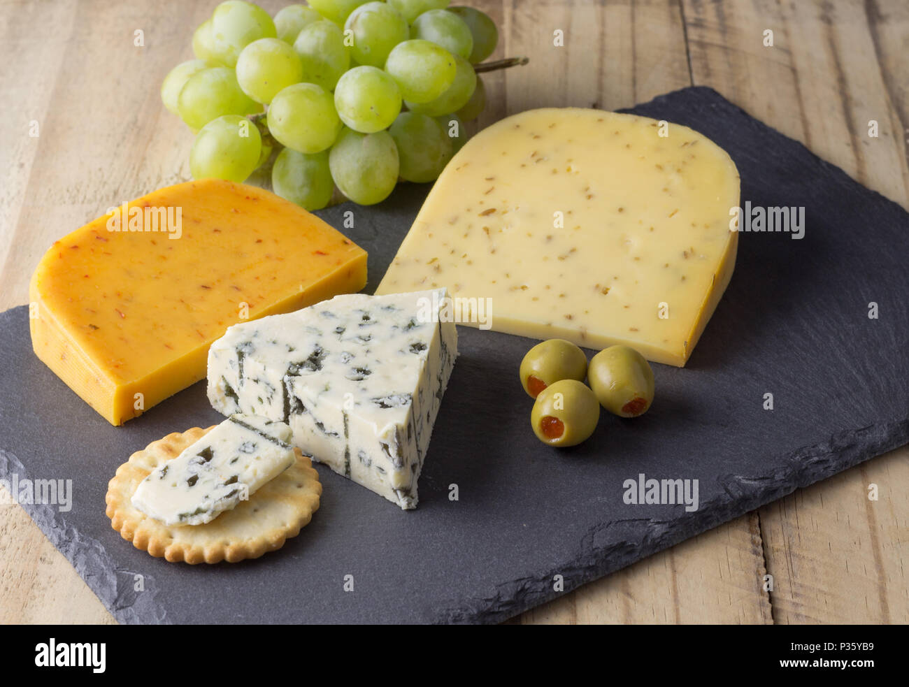 Cheese board with three cheeses, gouda with pimento, gouda with cumin seeds and roquefort blue cheese close up on rustic wooden background Stock Photo