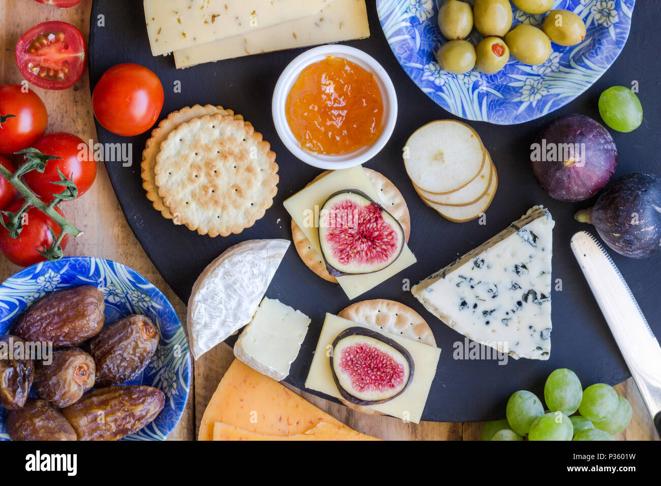 Cheese board close up with assortment of cheese, crackers, fruit and olives close up top view - Stock Image