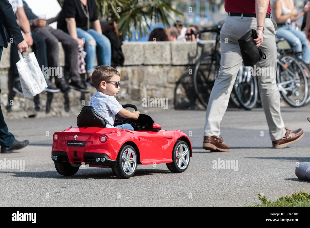 A little boy rolling in a small red car in the middle of the passers-by. This little car is a toy. Stock Photo
