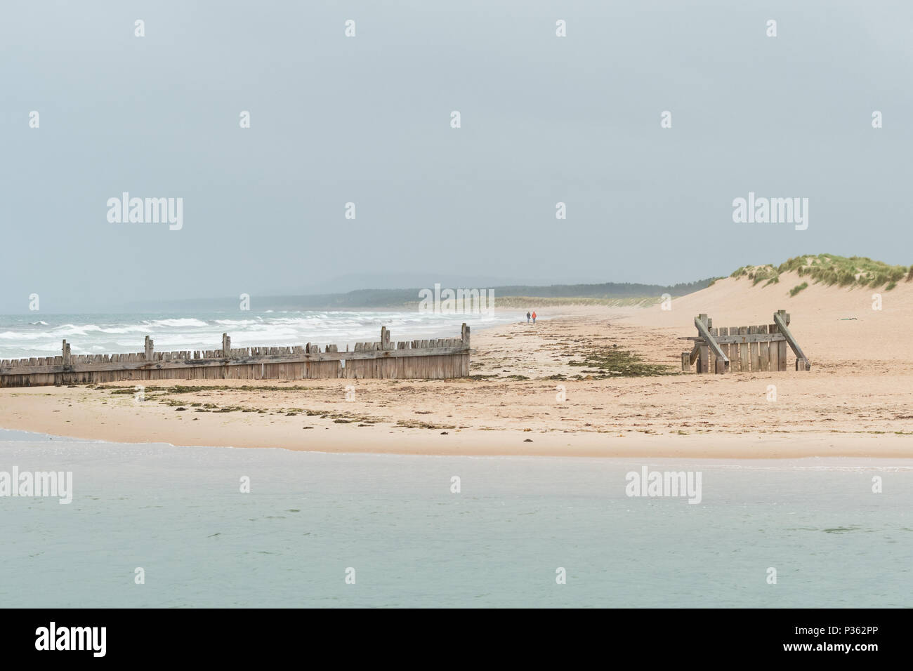 Lossiemouth - couple in distance walking along Lossiemouth East Beach towards wooden groynes and the River Lossie, Moray, Scotland, UK - Stock Image