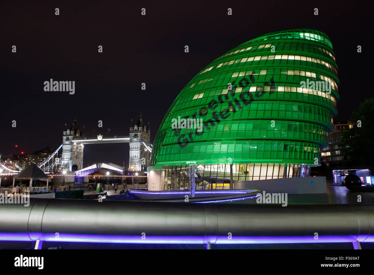 City Hall on the South Bank near Tower Bridge, lit green to mark the 1st anniversary of The Grenfell Tower Fire disaster. - Stock Image