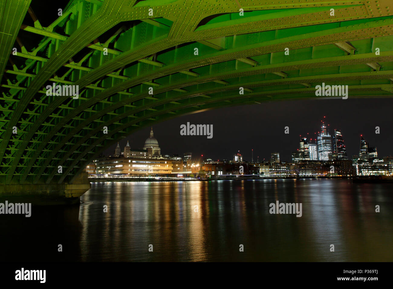 The city of London including Saint Pauls Cathedral from under Blackfriars Bridge, light-painted green with a powerful lamp - Stock Image