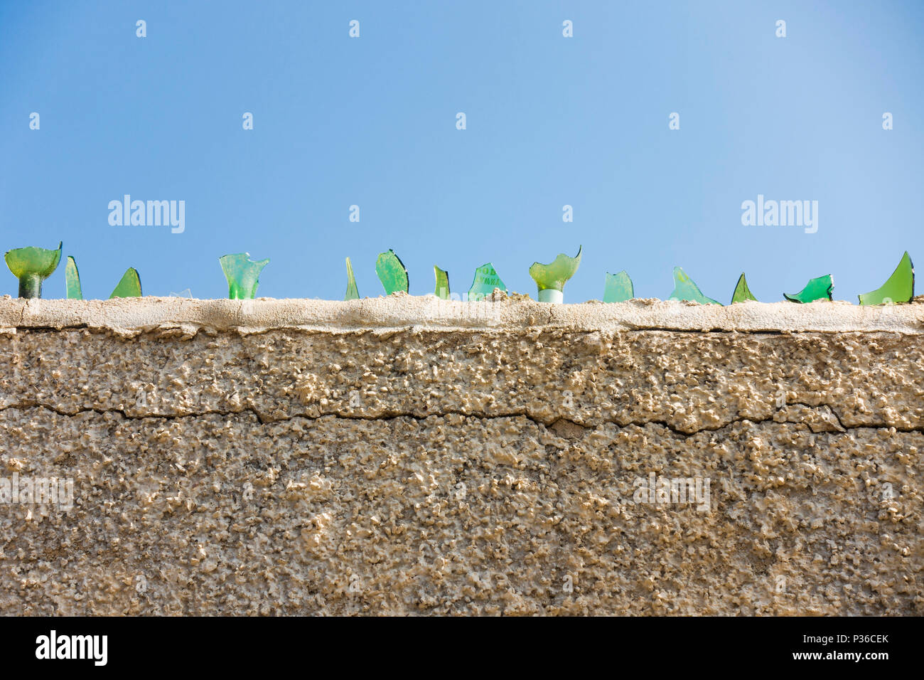 Glass shards on top of a wall for protection, Spain. - Stock Image