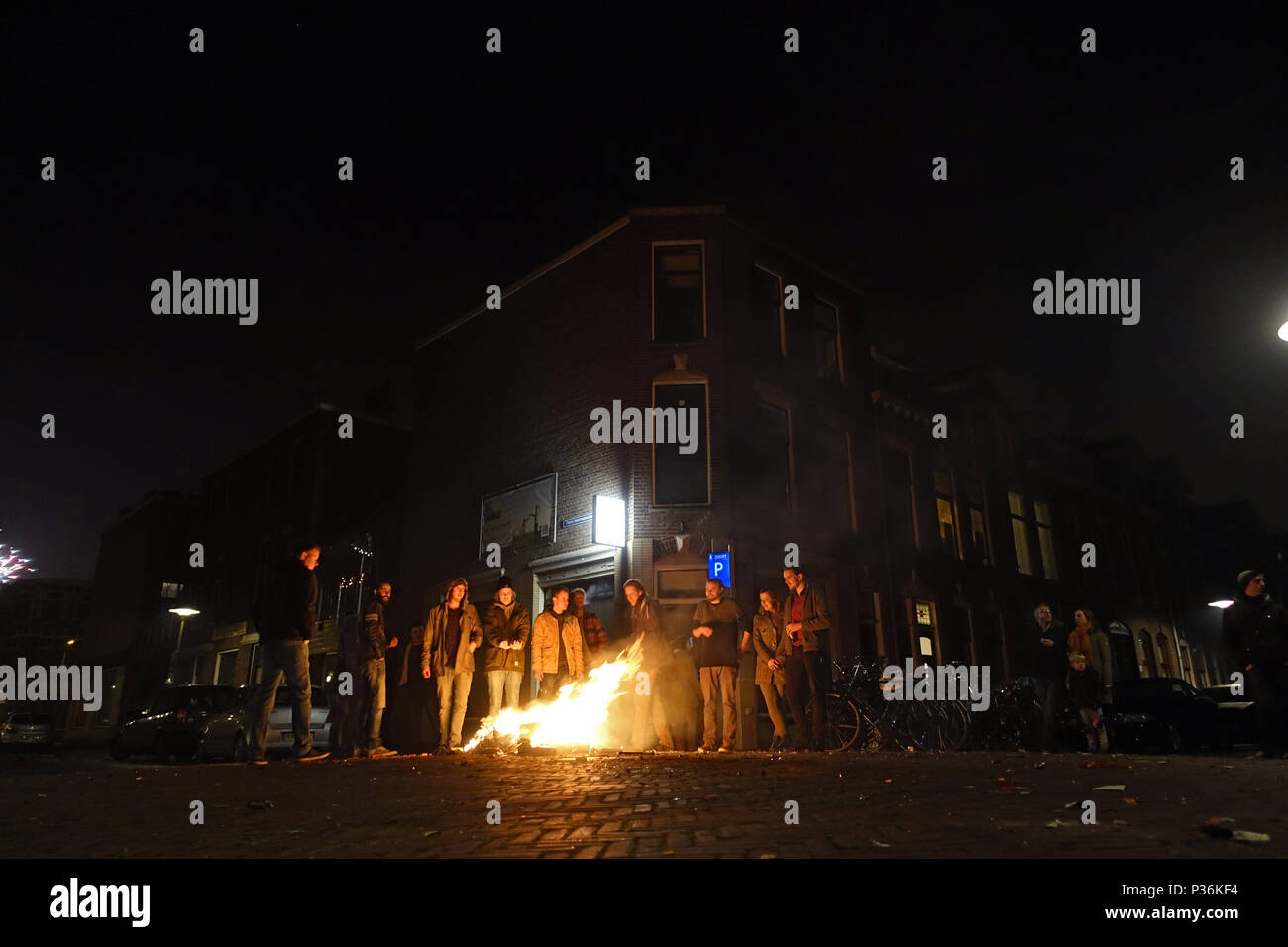 Utrecht, Netherlands, people are standing in the street in front of a small fire at night - Stock Image
