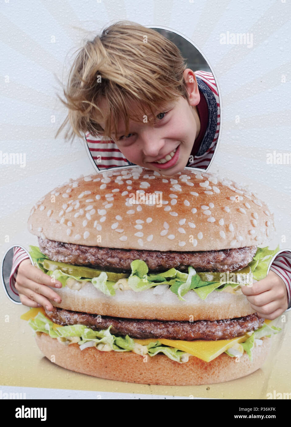Utrecht, Netherlands, boy pokes his head through a photo wall with the image of a burger - Stock Image